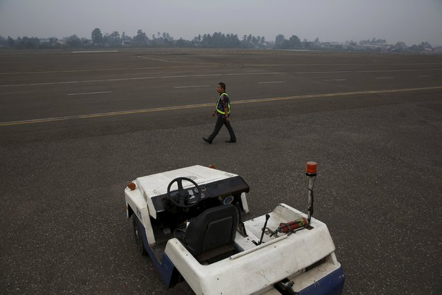 A Citilink airplane officer walks at an empty tarmac in Sultan Thaha airport as the haze shrouded Jambi, on Indonesia's Sumatra island, September 15, 2015. (Photo by Reuters/Beawiharta)