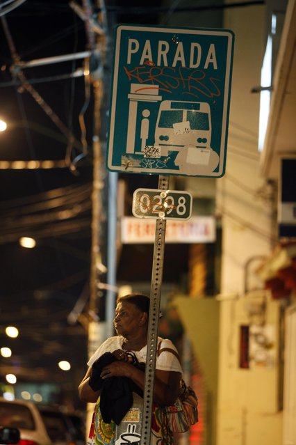 In this September 21, 2014 photo, a woman waits for public transportation at a bus stop in the Santurce neighborhood in San Juan, Puerto Rico. (Photo by Ricardo Arduengo/AP Photo)