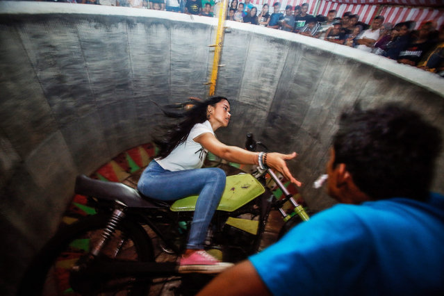 "A picture made available on 16 August 2016 shows a young dare devil motorbike rider, Karmila Purba, 18, reaching for a tip while riding her motorbike inside a barrel locally known as ""Tong Setan"" or Davil's Barrel, at a traditional night carnival in Deliserdang, North Sumatra, Indonesia, 13 August 2016. (Photo by Dedi Sinuhaji/EPA)"