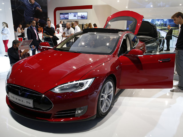 Visitors look at a Tesla Model S car displayed on media day at the Paris Mondial de l'Automobile, October 2, 2014. (Photo by Benoit Tessier/Reuters)