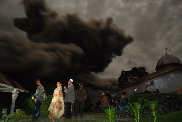 Residents gather outside their houses in Karo district as dark giant ash clouds, seen in the background, rise from the crater of Mount Sinabung volcano during an eruption late October 7, 2014 following an earlier eruption on October 5, 2014. According to authorities hundreds of residents are still housed at evacuation centers as authorities maintains off limit danger zone around Mount Sinabung located in Indonesia's Sumatra island following deadly eruption in early February that killed about 17 people. (Photo by Sutanta Aditya/AFP Photo)