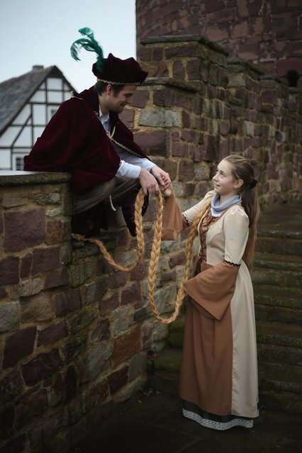 Rapunzel, actually 13-year-old actress Anna Helver, greets her prince, played by actor Daniel Stuebe, on a rampart of Trendelburg Castle on November 18, 2012 in Trendelburg, Germany. Rapunzel is one of the many stories featured in the collection of fairy tales collected by the Grimm brothers, and the 200th anniversary of the first publication of the stories will take place this coming December 20th. Anna and another actor perform a skit based on the Rapunzel tale to visitors at Trendelburg Castle, which is now a hotel, every Sunday. The Grimm brothers collected their stories from oral traditions in the region between Frankfurt and Bremen in the early 19th century, and the works include such global classics as Sleeping Beauty, Little Red Riding Hood, The Pied Piper of Hamelin, Cinderella and Hansel and Gretel.  (Photo by Sean Gallup)