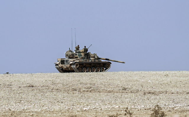A Turkish army tank stationed overlooks the Syrian border, in Karkamis, Turkey, Saturday, August 27, 2016. Turkey on Wednesday sent tanks across the border to help Syrian rebels retake the key Islamic State-held town of Jarablus and to contain the expansion of Syria's Kurds in an area bordering Turkey. (Photo by Halit Onur Sandal/AP Photo)