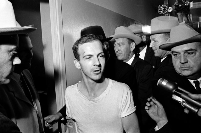 In this November 23, 1963, file photo, surrounded by detectives, Lee Harvey Oswald talks to the media as he is led down a corridor of the Dallas police station for another round of questioning in connection with the assassination of U.S. President John F. Kennedy. President Donald Trump is caught in a push-pull on new details of Kennedy's assassination, jammed between students of the killing who want every scrap of information and intelligence agencies that are said to be counseling restraint.  How that plays out should be known on Oct. 26, 2017, when long-secret files are expected to be released. (Photo by AP Photo)