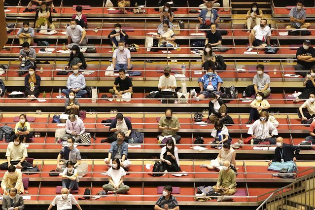 Sumo spectators wearing face mask practice social distance in their seats during the outbreak of the new coronavirus as they watch the first day of the sumo tournament in Tokyo, Sunday, July 19, 2020. (Photo by Kyodo News via AP Photo)
