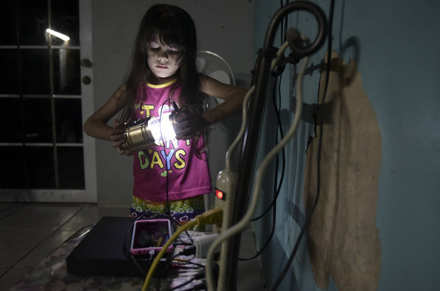 In this December 21, 2017 photo, six year old Melanie Oliveras Gonzalez holds a lantern in the living room of her house in Sector Padre Ibañes, in Morovis, Puerto Rico. All electronics are connected at night to an inverter plugged to the family car battery. (Photo by Carlos Giusti/AP Photo)