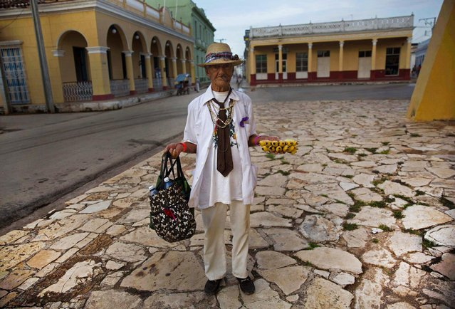 In this September 1, 2016 photo, 90-year-old street vendor Antonio Bauza waits for tourists to sell his bananas, next to the village church in Remedios, Cuba. With the arrival of the first commercial flights from the U.S. to Cuba in more than 50 years, the Cuban government is welcoming the wave of new visitors and struggling to update infrastructure that's already overwhelmed. (Photo by Ramon Espinosa/AP Photo)