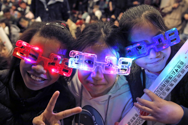 Residents wear 2018 glasses, during New Year's Eve to celebrate the upcoming year 2018 in Hong Kong, Sunday, December 31, 2017. (Photo by Kin Cheung/AP Photo)