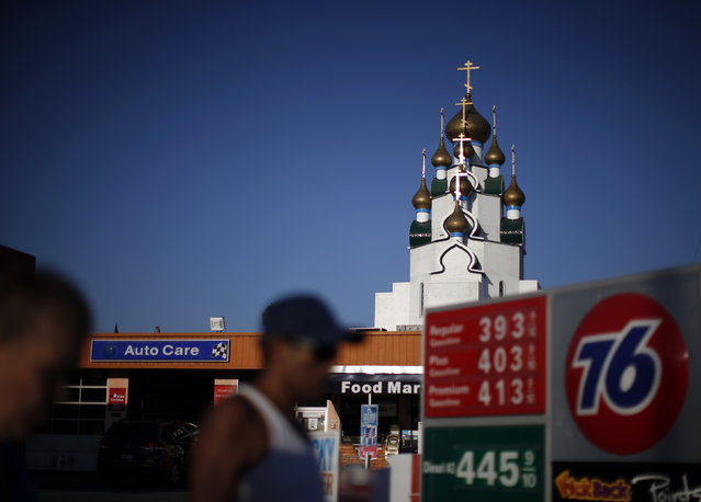 People walk past a gas station as a Russian Orthodox Church is seen in the distance in Hollywood, California August 11, 2014. (Photo by Lucy Nicholson/Reuters)