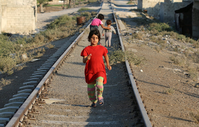A girl walks along a broken railway track in the rebel-held al-Sheikh Said neighbourhood of Aleppo, Syria September 1, 2016. (Photo by Abdalrhman Ismail/Reuters)