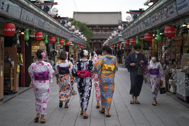 Tourists in traditional Japanese kimonos walk in Asakusa district in Tokyo Monday, July 27, 2020. The Japanese capital confirmed Monday more than 100 new coronavirus cases. (Photo by Eugene Hoshiko/AP Photo)