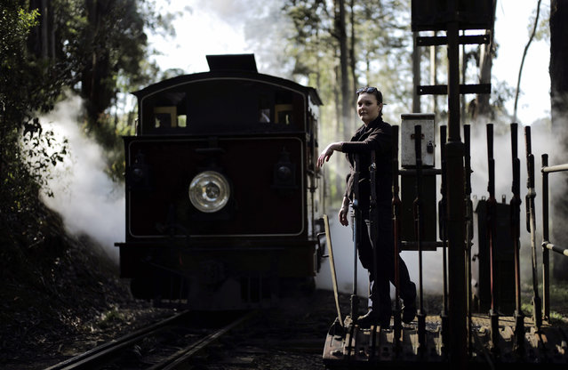 Puffing Billy steam railway guard Emma Pallister leans on the levers used to switch tracks as steam engine 12A passes by at Belgrave station near Melbourne, October 20, 2014. (Photo by Jason Reed/Reuters)