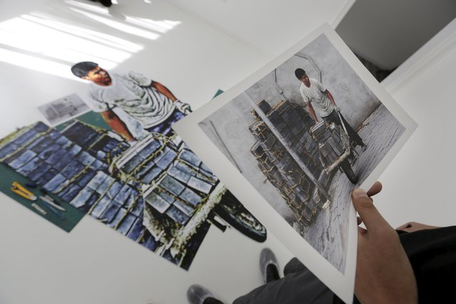 Chinese artist ROBBBB checks a picture of a construction worker as he makes his artpiece in his studio in Beijing October 1, 2015. (Photo by Jason Lee/Reuters)