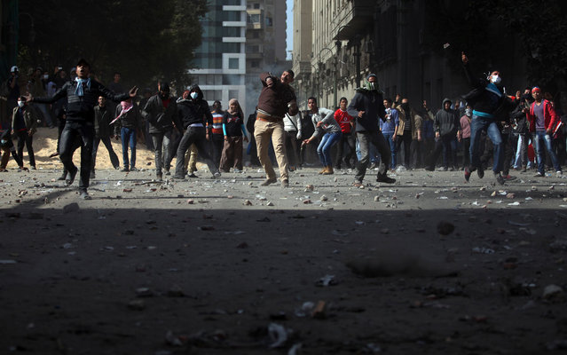 Egyptian protesters throw stones at riot police, not seen, during clashes near Tahrir Square, on January 25, 2013. (Photo by Khalil Hamra/AP Photo/The Atlantic)