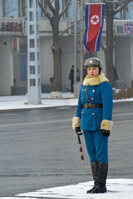 A traffic police officer, dressed in blue uniform with a fur trim, performs her duty in the capital in February 2013, in Pyongyang, North Korea. (Photo by Andrew Macleod/Barcroft Media)
