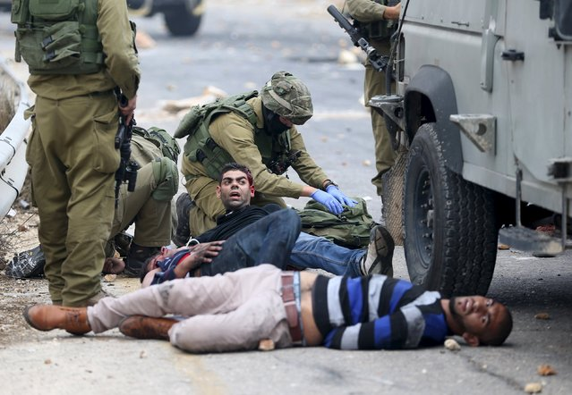 Israeli soldiers detain wounded Palestinian protesters during clashes near the Jewish settlement of Bet El, near the West Bank city of Ramallah, October 7, 2015. Israeli Prime Minister Benjamin Netanyahu has cancelled a trip to Germany planned for Thursday, German government sources told Reuters, as tensions rise between Palestinians and Israelis after about 10 days of violence. (Photo by Mohamad Torokman/Reuters)
