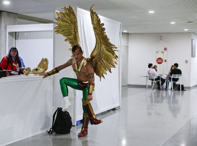 Diego Vargas puts on the boots to his Hawkman costume while attending New York Comic Con, Thursday, October 8, 2015, in New York. The pop culture convention, featuring the latest in comics, graphic novels, anime, manga, video games, toys, movies and television, runs through Sunday. (Photo by Julie Jacobson/AP Photo)