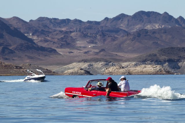 A speedboat passes by a 1963 Amphicar, driven by Rob Vondracek of Fountain Hills, Arizona, during the first Las Vegas Amphicar Swim-in at Lake Mead near Las Vegas, Nevada October 9, 2015. (Photo by Steve Marcus/Reuters)
