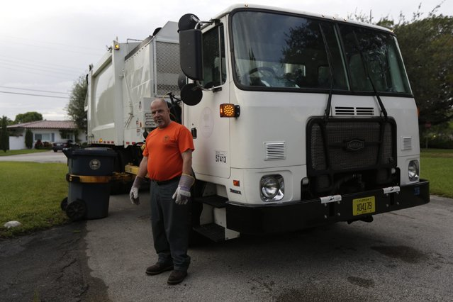 Former Cuban rafter Pedro Brea, 50, poses while working as a municipal garbage collector in Miami, September 18, 2014. Brea said he spent three days clinging to a sinking raft in the middle of a storm when a U.S. Navy frigate picked him up from the sea in 1994. (Photo by Rolando Pujol Rodriguez/Reuters)