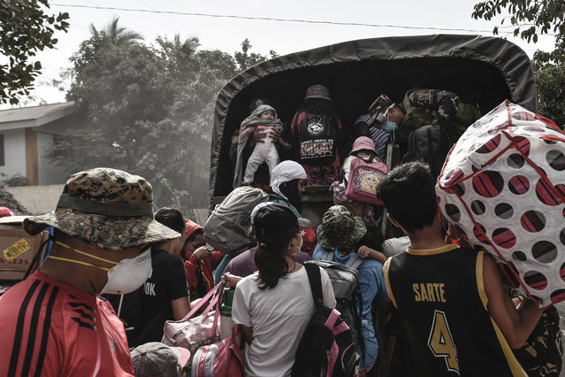 Residents flock to board a military truck as they flee the nine kilometer extended danger zone around Mount Mayon in Guinobatan, Albay province, Philippines, January 23, 2018. (Photo by Ezra Acayan/NurPhoto via Getty Images)