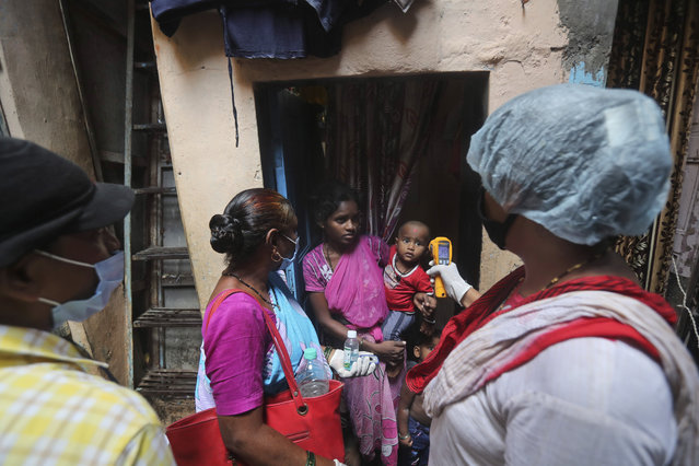 A health worker screens people for symptoms of COVID-19 in Dharavi, one of Asia's biggest slums, in Mumbai, India, Tuesday, September 8, 2020. India's coronavirus cases are now the second-highest in the world and only behind the United States. (Photo by Rafiq Maqbool/AP Photo)