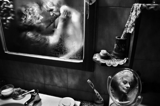 """This image by Fausto Podavini, Italy, from the series """"Mirella"""" won 1st prize in the Daily Life Stories category of the 56th World Press Photo Contest, it was announced by the organizers in Amsterdam, The Netherlands, on 15 February 2013. It shows Mirella taking care of her husband Luigi, who suffers from Alzheimer's disease, in Rome, Italy, 01 June 2010. Despite her husband's life-threatening disease, Mirella devoted her life to assisting Luigi, trying to be positive and reassuring, looking after him with intense love and respect. Everyday care, usually done in a few minutes, takes hours when it concerns someone with dementia. Mirella, 71, spent 43 years of her life with the only person she loved, with all of life's difficulties, laughter, and beautiful moments. But over the last six years things changed: Mirella lived with her husband Luigi's illness, Alzheimer's, and devoted her life to him as his caregiver. (Photo by Fausto Podavini/EPA)"""