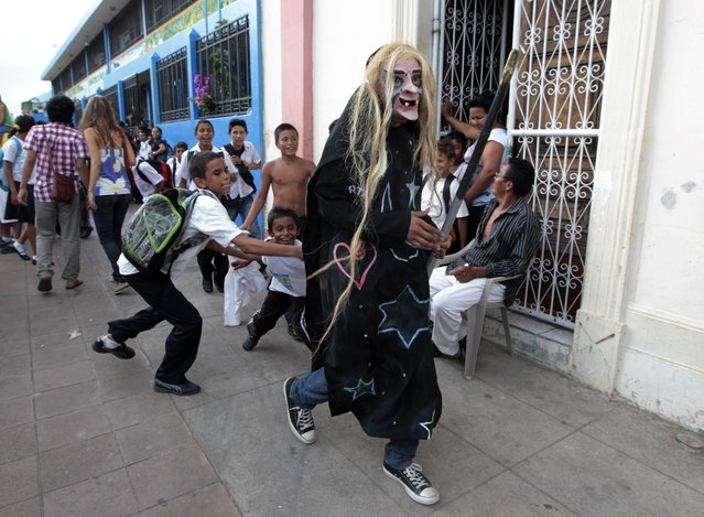 A masked reveller runs through the street during the IX International Festival of Poetry in Granada city, about 45 km (28 miles) south of Managua, February 20, 2013. About 300 poets from around the world along with Nicaraguans participated in the IX international poetry festival dedicated to Nicaraguan poet Ernesto Cardenal who won the Queen Sofia Prize of 2012. (Photo by Oswaldo Rivas/Reuters)
