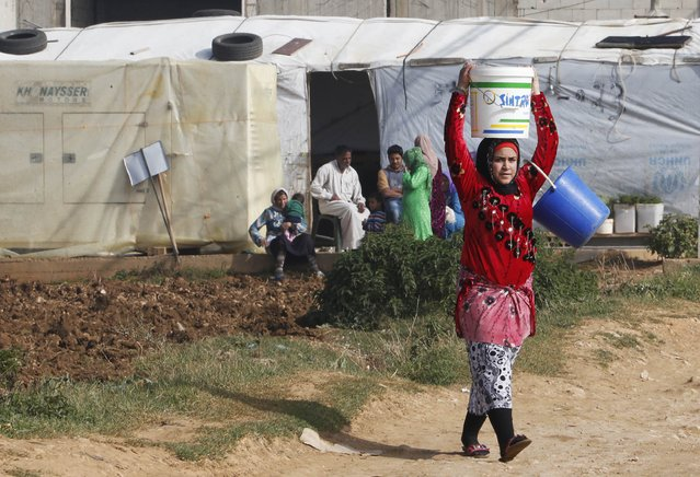 A Syrian refugee girl carries a bucket of water as she walks past tents at a refugee camp in Zahle in the Bekaa valley November 18, 2014. (Photo by Mohamed Azakir/Reuters)