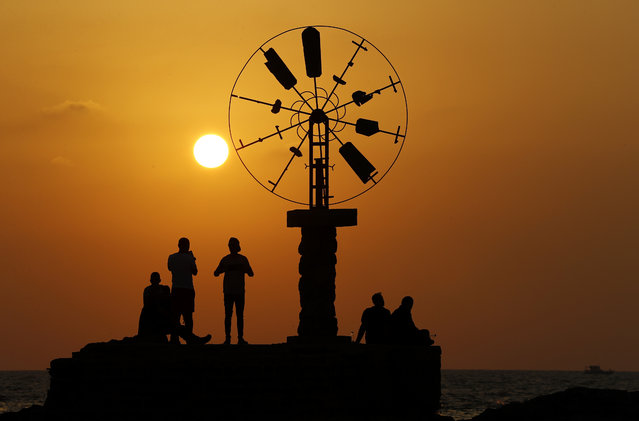 Lebanese citizens stand next to a windmill while watching the sunset, at the coast of Tripoli city, north of Lebanon, Thursday, September 17, 2020. (Photo by Hussein Malla/AP Photo)
