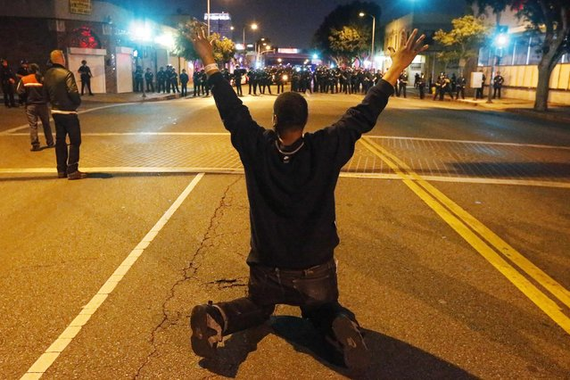 A man kneels in the road in front of a line of police during a demonstration in Los Angeles, California November 24, 2014, following the grand jury decision in the shooting of Michael Brown in Ferguson, Missouri. (Photo by Lucy Nicholson/Reuters)