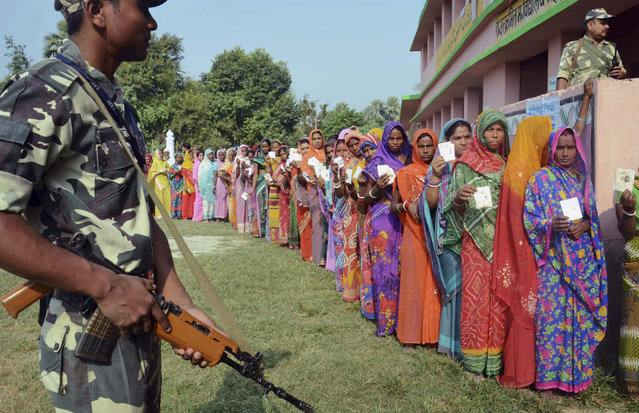 Indian security personnel guard as women voters stand in a queue to cast their votes at a polling station during the first of the five phase voting for state legislative assembly at Mahmoodpur village, in Samastipur district of India's eastern state Bihar, Monday, October 12, 2015. (Photo by Aftab Alam Siddiqui/AP Photo)