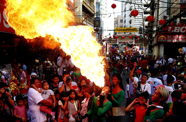 A fire-eater performs on the street in celebration of the Chinese Lunar New Year Friday, February 16, 2018 at Manila's Chinatown district, Philippines. (Photo by Bullit Marquez/AP Photo)