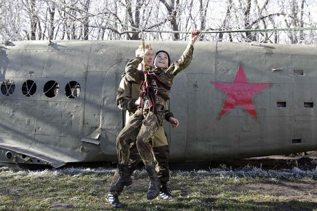 A student from the General Yermolov Cadet School crosses an obstacle during a competition between school classes in the southern Russian city of Stavropol, November 22, 2014. The General Yermolov Cadet School in Stavropol is a state-run institution that teaches military and patriotic classes in addition to a normal syllabus. (Photo by Eduard Korniyenko/Reuters)
