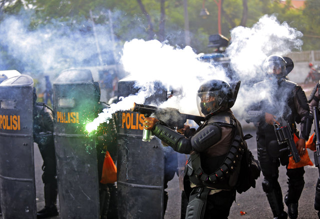 A police officer fires his tear gas launcher during a clash with student protesters in Surabaya, East Java, Indonesia, Thursday, October 8, 2020. Thousands of enraged students and workers staged rallies across Indonesia on Thursday in opposition to the new law they say will cripple labor rights and harm the environment. (Photo by Trisnadi/AP Photo)