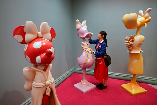 """A staff member wearing a face mask cleans an artwork with disinfectant in the new """"Minnie's Style Studio"""" at Tokyo Disneyland in Urayasu, east of Tokyo, Japan, 25 September 2020. Tokyo Disneyland unveiled to the media the new """"Beauty and the Beast"""" area with special arrangements to prevent the spread of the coronavirus amid the COVID-19 disease pandemic. The new installations and attractions will open to the public on 28 September. (Photo by  Franck Robichon/EPA/EFE)"""