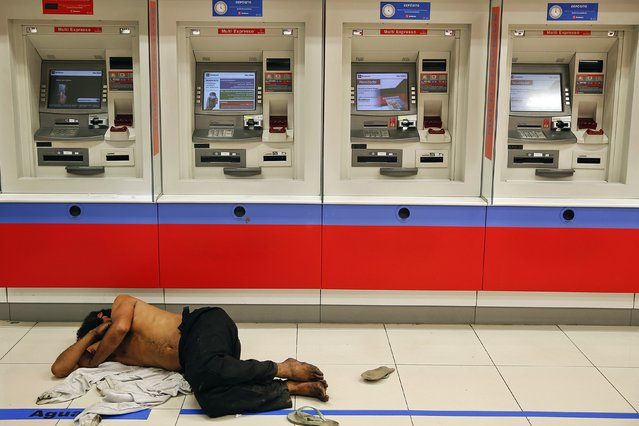 A man sleeps in front of ATM machines on Paulista Avenue in central Sao Paulo, in this June 8, 2014 file photo. (Photo by Damir Sagolj/Reuters)