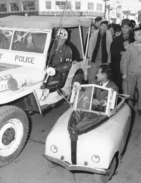 John F. Daniels, T/5 of Allentown, Pa., an MP motor patrol, inspects the electrically-powered midget auto, designed by a former kamikaze pilot, during its first public run in Tokyo, December 21, 1947. (Photo by Charles Gorry/AP Photo)