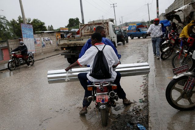 Men carry metal sheets on a motorcycle while Hurricane Matthew approaches Port-au-Prince, Haiti, October 3, 2016. (Photo by Carlos Garcia Rawlins/Reuters)