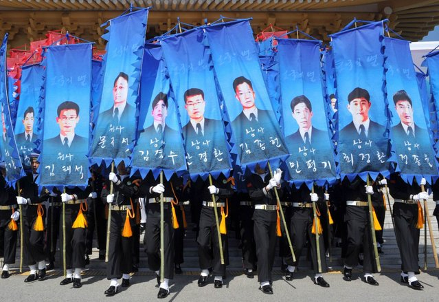 South Korean honour guards hold banners with pictures of the sailors who died in the sinking of a South Korean naval vessel by what Seoul insists was a North Korean submarine, during an event marking the third anniversary of the incident, at the national cemetery in Daejeon March 26, 2013. 46 sailors died when the Cheonan corvette sunk. (Photo by Kim Jae-Hwan/Reuters)