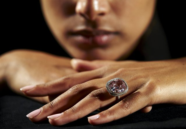 An employee poses with a cushion-shaped 16.08 carat vivid pink diamond at Christie's auction house in Geneva, Switzerland October 30, 2015. The diamond is estimated to sell for $23-28 million when auctioned during the Magnificent Jewels auction in Geneva on November 10. The stone is set as a ring, that includes a double row of pave-set white diamonds that border and accentuate the main stone, along with a third row of small pink diamonds beneath. (Photo by Denis Balibouse/Reuters)