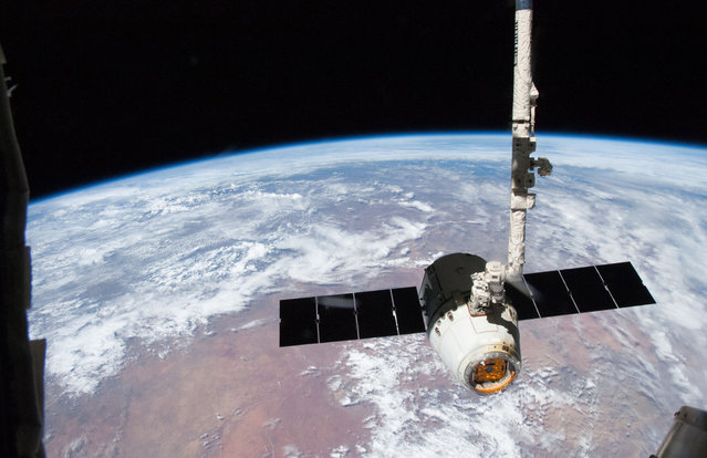 The release the SpaceX Dragon-2 spacecraft from the International Space Station on March 26, 2013. The spacecraft, filled with experiments and old supplies, is in the grasp of the Space Station Remote Manipulator System's robot arm or CanadArm2 after it was undocked from the orbital outpost. Forming the backdrop for this image is western Namibia. The Dragon was scheduled to make a landing in the Pacific Ocean, off the coast of California later in the day. (Photo by NASA/The Atlantic)