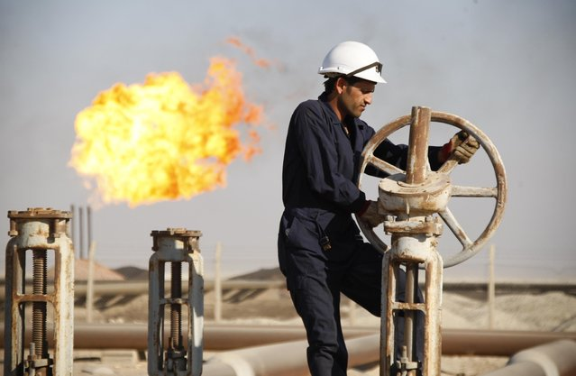 A worker adjusts the valve of an oil pipe at West Qurna oilfield in Iraq's southern province of Basra in this November 28, 2010 file photo. (Photo by Atef Hassan/Reuters)