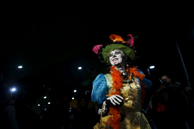 "A woman dressed up as ""Catrina"", a Mexican character also known as ""The Elegant Death"", smiles during a Catrinas parade in Mexico City October 31, 2015. Mexicans are preparing to celebrate Day of the Dead on November 1 and 2. (Photo by Carlos Jasso/Reuters)"