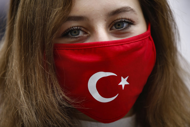 """A woman, wearing a Turkish flag-decorated mask to help curb the spread of the coronavirus, near France's consulate in Istanbul, Wednesday, October 28, 2020. Turkish officials railed against French satirical magazine Charlie Hebdo over its cover-page cartoon mocking Turkish President Recep Tayyip Erdogan and accused it of sowing """"the seeds of hatred and animosity."""" The cartoon could further heighten tensions between Turkey and France, which erupted over French President Emmanuel Macron's firm stance against Islamism following the beheading of a teacher who showed his class caricatures of the Prophet Muhammad for a free speech class. (Photo by Emrah Gurel/AP Photo)"""