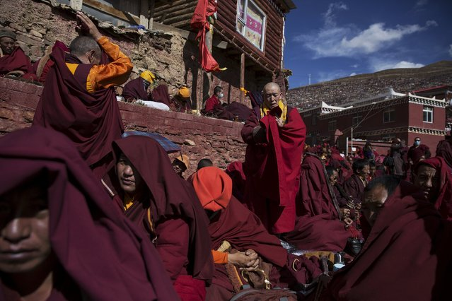 Tibetan Buddhist monks pray at Buddhist laymen lodge where thousands of people gather for daily chanting session during the Utmost Bliss Dharma Assembly, the last of the four Dharma assemblies at Larung Wuming Buddhist Institute in remote Sertar county, Garze Tibetan Autonomous Prefecture, Sichuan province, China October 30, 2015. (Photo by Damir Sagolj/Reuters)