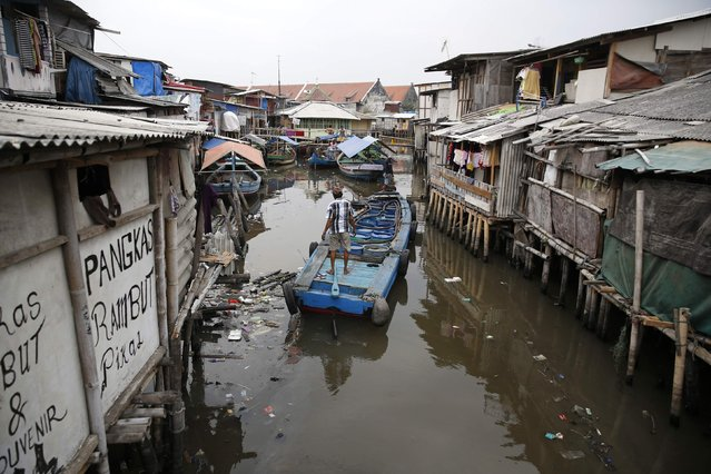 A boat passes through a canal along houses built over the  seawall protecting Luar Batang, one of the oldest kampongs in Jakarta, dating back to the16th century, in north Jakarta October 7, 2014. (Photo by Darren Whiteside/Reuters)