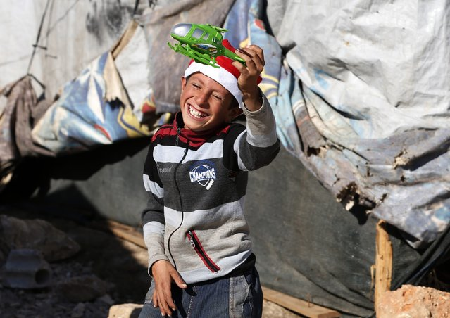A Syrian refugee child plays with his Christmas gift from SAWA, a non-governmental organisation, in Bar-Elias in the Bekaa valley December 24, 2014. (Photo by Jamal Saidi/Reuters)