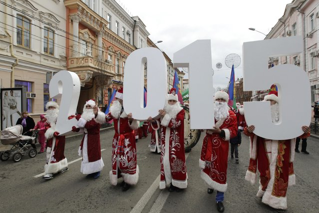 People dressed as Father Frost, the equivalent of Santa Claus, carry figures that make up the number 2015 during a parade in the Russian southern city of Krasnodar December 20, 2014. (Photo by Eduard Korniyenko/Reuters)