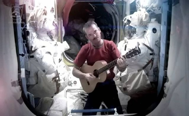 Handout grab taken from YouTube of Commander Chris Hadfield who has said goodbye to life on the International Space Station by making a cover version of David Bowie's Space Oddity. Issue date: Monday May 13, 2013. (Photo by Commander Chris Hadfield/YouTube/PA Wire)