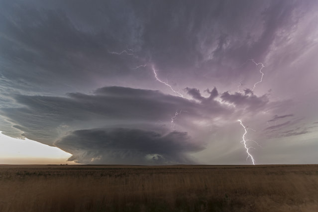 A tornadic storm strikes lightning over the prairies as hail the size of baseballs fall from the cloud, on July 22, 2014, in South Dakota. (Photo by Roger Hill/Barcroft Media)